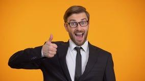 Gelukkige mens in kostuum die duimen tonen en naar camera, goed voorstel knipogen stock videobeelden