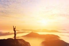 Gelukkige mens met handen omhoog op de bovenkant van de wereld boven wolken Rooskleurige Toekomst Stock Foto