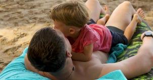 Gelukkige mens met jong geitje op strand stock videobeelden