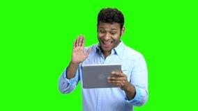 Gelukkige mens met tabletpc die videopraatje hebben stock video