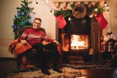 Gelukkige mens in rode sweaterzitting voor de open haard stock afbeeldingen