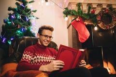 Gelukkige mens in rode sweaterzitting voor het open haard en holdingsboek stock fotografie