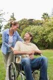Gelukkige mens in rolstoel die met partner spreken stock afbeeldingen