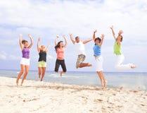 Gelukkige mensen die op het strand springen Royalty-vrije Stock Afbeelding