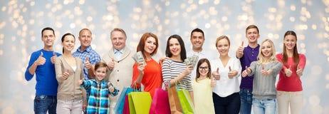 Gelukkige mensen met het winkelen zakken en geld Stock Foto
