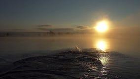Gelukkige mensenlooppas en jumns in een meer bij zonsondergang in slo-mo stock video