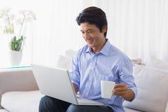 Gelukkige mensenzitting op laag die laptop met behulp van die koffie hebben royalty-vrije stock afbeelding