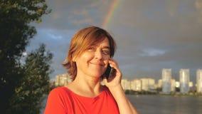 Gelukkige midden oude vrouw met mobiele status dichtbij meer en het glimlachen Regenboog stock video