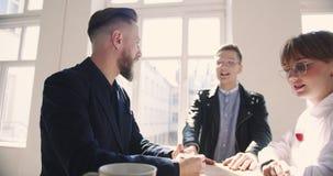 Gelukkige midden oude zakenman die aan jonge medemedewerkers op comfortabel licht in kantoor, gezonde werkplaats spreken stock videobeelden