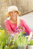 Gelukkige middenleeftijdsvrouw met bloemen in haar tuin royalty-vrije stock foto's