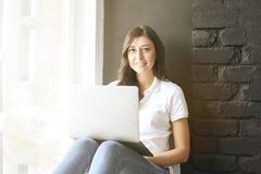 Gelukkige millennial meisjesw laptop op vensterbank Portret van jonge vrouw met diastemahiaat tussen tanden Mooie glimlach minima royalty-vrije stock foto's