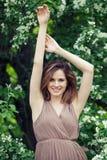 Gelukkige modelvrouw in park op bloemen de lenteachtergrond, levensstijlportret stock foto