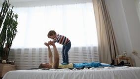 Gelukkige moderne familie De papa met een kleine zoon heeft pret op het bed in de slaapkamer stock footage