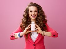 Gelukkige moderne vrouw op roze die landbouwbedrijf organische yoghurt tonen stock foto's