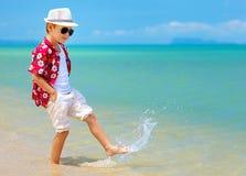 Gelukkige modieuze jong geitjejongen die in branding op tropisch strand lopen Stock Afbeeldingen
