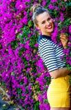 Gelukkige modieuze vrouw tegen kleurrijk magenta bloemenbed royalty-vrije stock foto's