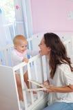Gelukkige moeder die bij baby in voederbak glimlachen stock foto's