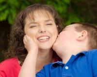 Gelukkige moeder die bij kus van zoon glimlachen Stock Foto's