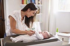 Gelukkige moeder die de luier van haar pasgeboren zoon thuis op een baby veranderende lijst veranderen, taille omhoog royalty-vrije stock foto