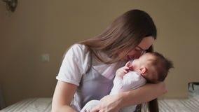 Gelukkige moeder die een baby in haar wapens en zacht kussen houden stock footage