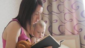 Gelukkige moeder die een boek binnen lezen aan kindjongen Zoet ogenblik met het boek van de moederlezing aan baby stock video