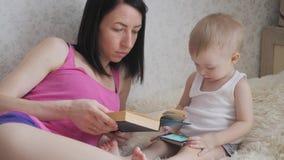 Gelukkige moeder die een boek binnen lezen aan kindjongen Zoet ogenblik met het boek van de moederlezing aan baby stock videobeelden
