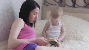 Gelukkige moeder die een boek binnen lezen aan kindjongen Zoet ogenblik met het boek van de moederlezing aan baby stock footage