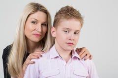 Gelukkige moeder die een zoon met slordig haar koesteren Stock Fotografie