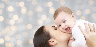 Gelukkige moeder die haar baby over lichten kussen Stock Foto's
