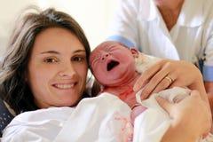 Gelukkige moeder die haar baby, seconden houden nadat zij een geboorte, n gaf Stock Afbeelding