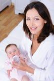 Gelukkige moeder die haar baby voedt Stock Foto's