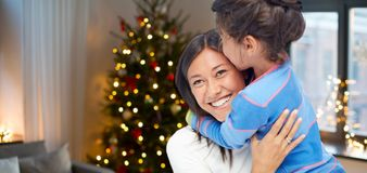 Gelukkige moeder die haar dochter op Kerstmis koesteren royalty-vrije stock afbeeldingen