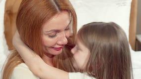 Gelukkige moeder die haar koesteren weinig dochter koesteren, die aan de camera glimlachen stock footage