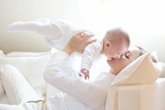 Gelukkige moeder die haar mooie glimlachende baby houden Stock Foto's