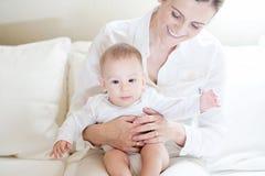 Gelukkige moeder die haar mooie glimlachende baby houden Royalty-vrije Stock Afbeeldingen