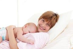 Gelukkige moeder die haar pasgeboren baby omhelst Stock Afbeeldingen