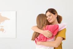 Gelukkige moeder die haar tienerdochter koestert stock afbeelding