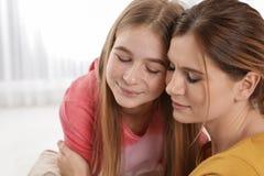 Gelukkige moeder die haar tienerdochter koestert royalty-vrije stock afbeeldingen