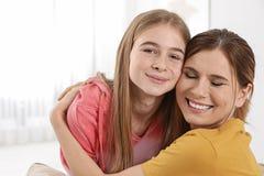 Gelukkige moeder die haar tienerdochter koestert stock fotografie