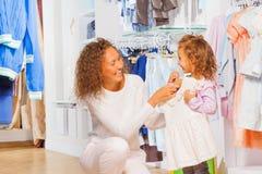 Gelukkige moeder die kleding op haar dochter proberen Stock Fotografie