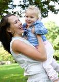 Gelukkige moeder die leuke babydochter in openlucht houden Royalty-vrije Stock Foto's