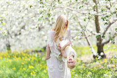 Gelukkige Moeder die met Babydochter dansen in Bloeiend Apple Orcha Stock Foto's