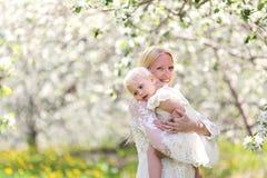 Gelukkige Moeder die met Babydochter dansen in Bloeiend Apple Orcha Stock Fotografie
