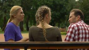Gelukkige moeder die met dochter en echtgenoot in park, het gekscheren en het lachen spreken stock footage