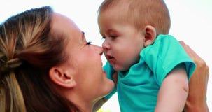 Gelukkige moeder die neuzen met leuke babyzoon wrijven in het park stock video