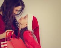 Gelukkige moeder die op haar leuke dochter in de hoed van de Kerstman kijken en Kerstmis huidige pakketten houden stock foto's
