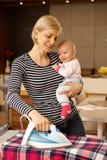 Gelukkige moeder die terwijl het houden van baby strijken stock afbeeldingen