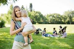 Gelukkige Moeder Dragende Dochter bij Park Royalty-vrije Stock Afbeelding