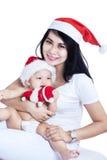 Gelukkige moeder en baby in rode Kerstmishoeden stock afbeeldingen