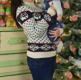 Gelukkige moeder en de aanbiddelijke snuisterij van de babyholding tegen binnenlandse feestelijke achtergrond met Kerstboom royalty-vrije stock fotografie
